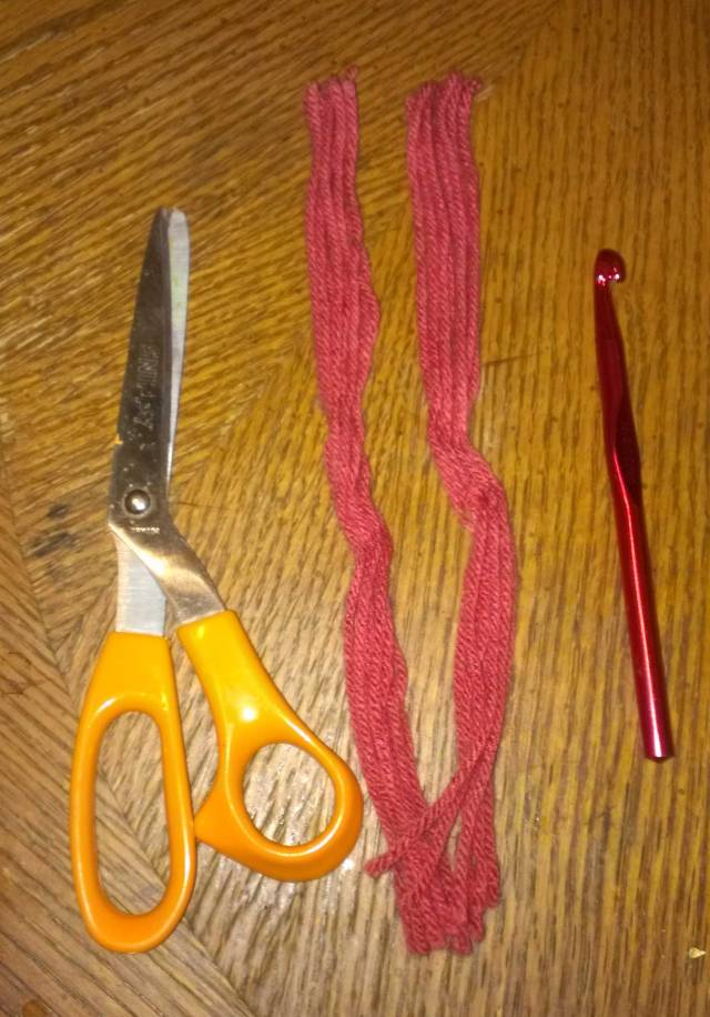 Your tools: scissors, your fringe, which I advise pre-cutting before you sit down to add it, and a crochet hook (I used a size N - 9.00 mm