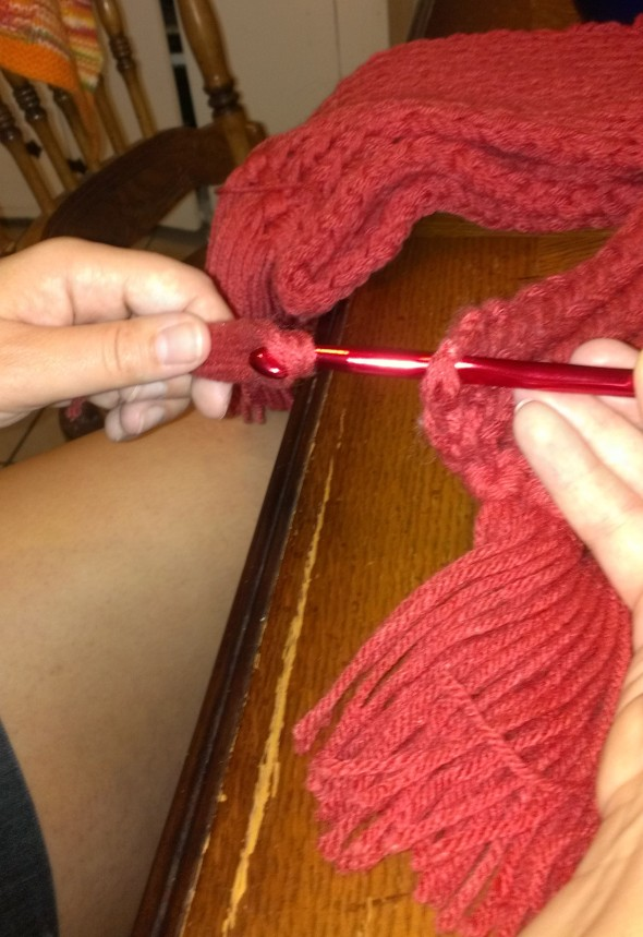 Folding the strands of fringe in half, use the crochet hook to pull them through the edge from right to wrong side.