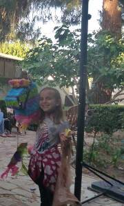 A happy birthday girl with the remains of her pinata. Double digits from here on out!